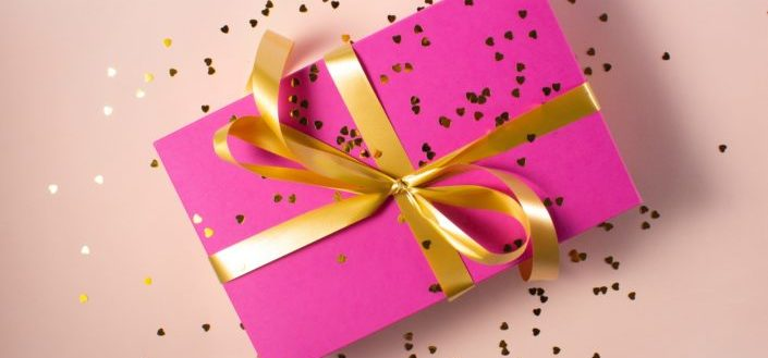A pink gift box wrapped in gold ribbon