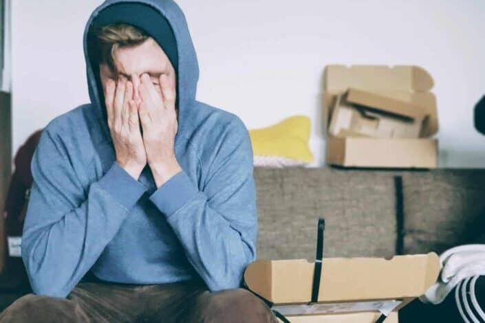 Man in hoodie hiding with his hands