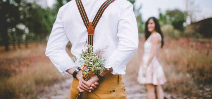 Guy hiding a bouquet of flowers to give to the girl.