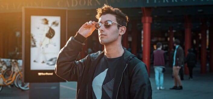Man in black zip-up jacket wearing sunglasses