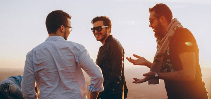 Three male friends talking about something while outdoors.