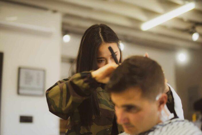 A woman trimming a man's hair