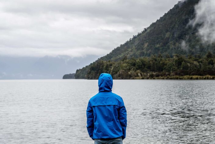 person wearing blue hoodie near the sea