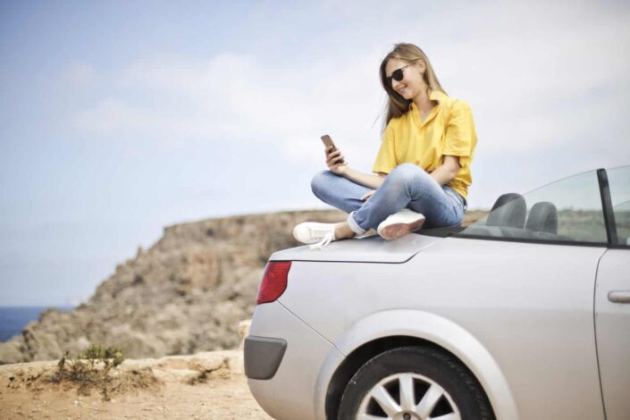 Girl sitting on top of car and reading her text