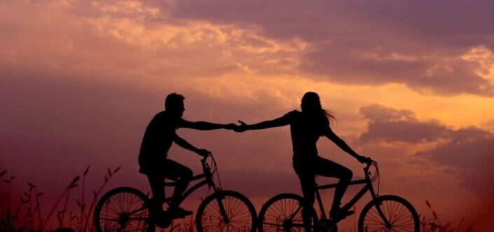 Silhouette of a couple holding hands while riding bikes