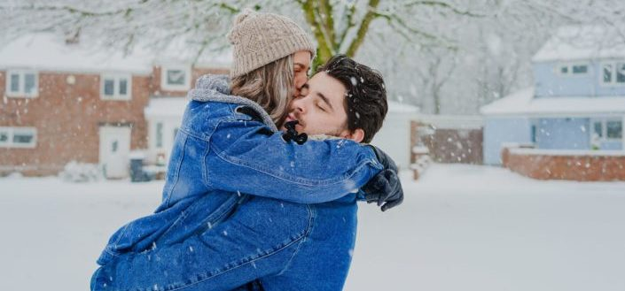 A man carrying a woman that is kissing him while it's snowing