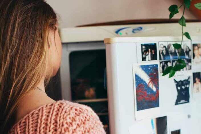 A woman looking inside a refrigerator