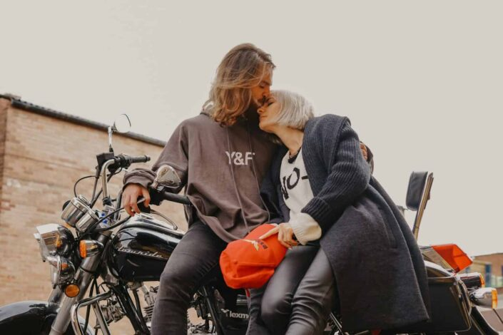A man kissing a woman on the forehead while sitting on a motorcycle