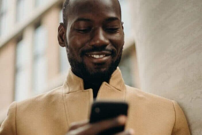 A man smiling at his phone while he's holding it