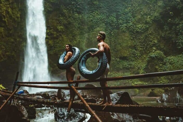 A couple with tires walking towards waterfalls
