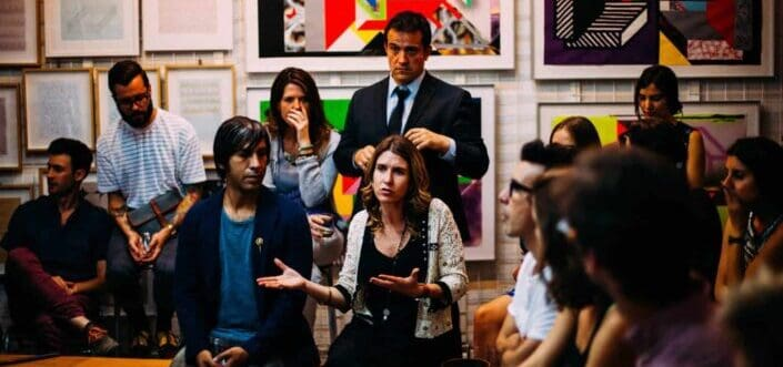 Woman surrounded by colleagues while explaining.