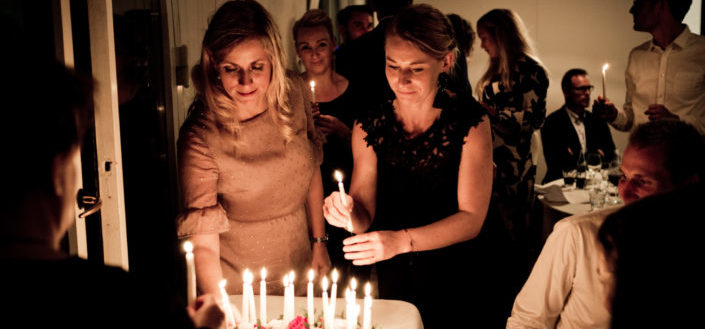 Two women holding candles by a cake
