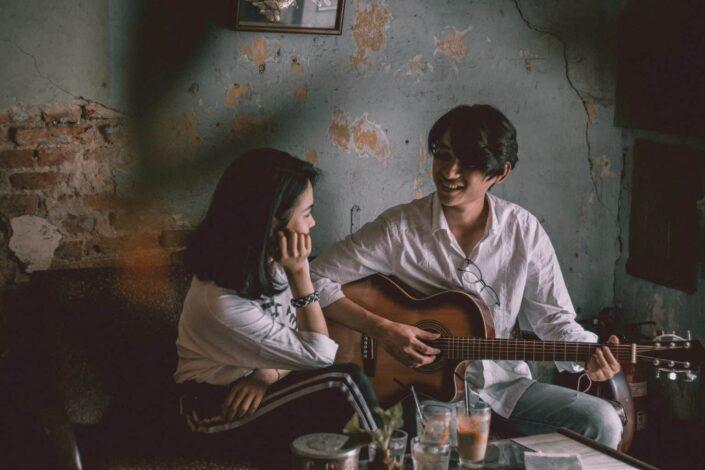 Man playing guitar while staring at the girl.