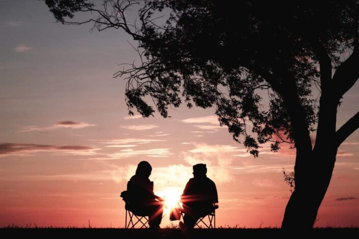 two people watching the sunset while talking