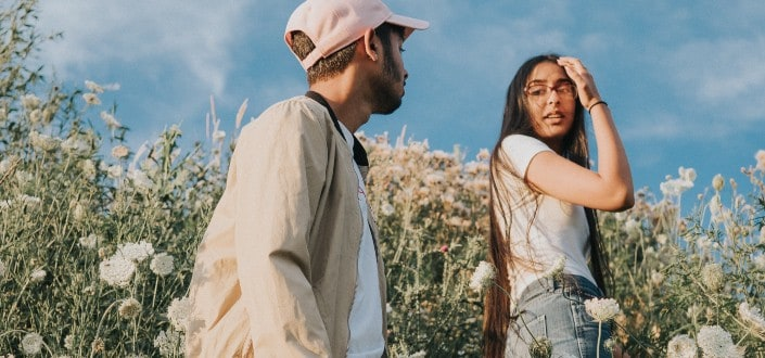 man looking at woman in a field of flowers