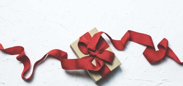 Brown gift wrapped with a red ribbon.