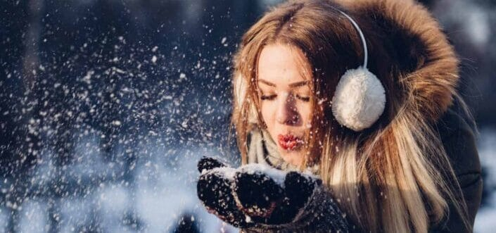 Woman blowing a handful of snow.