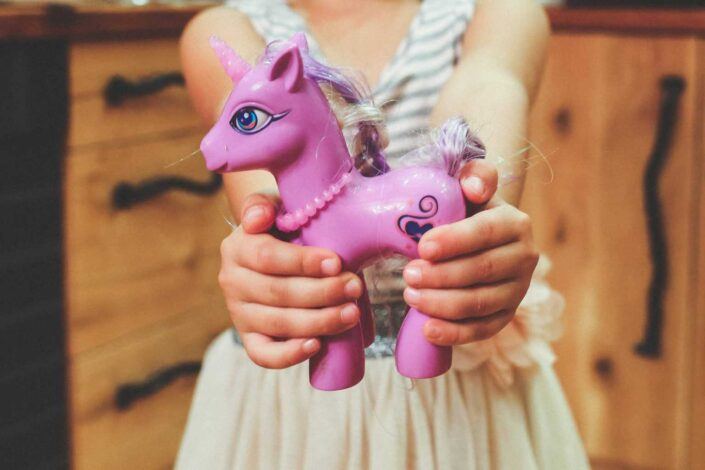 Young girl holding a My Little Pony toy