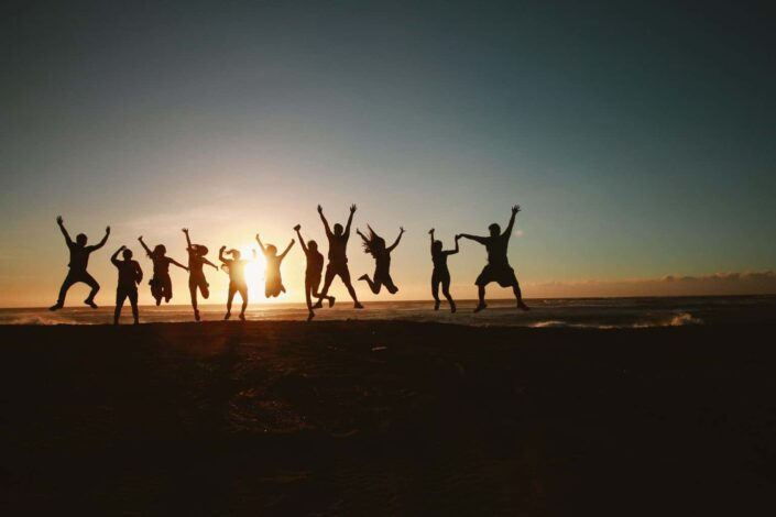 silhouette photography of people jumping during golden time