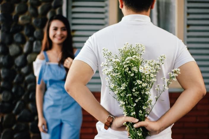 Man holding baby's breath flower in his back