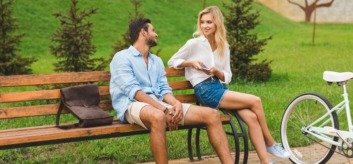 Couple having conversation while resting on bench after walk in park