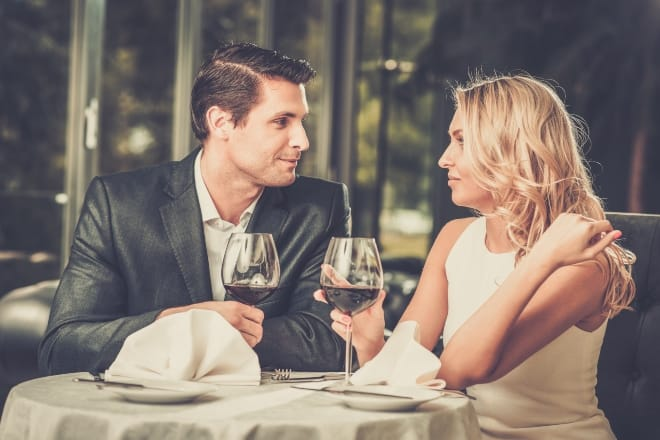 How to Ask A Girl Out - Cheerful couple in a restaurant with glasses of red wine