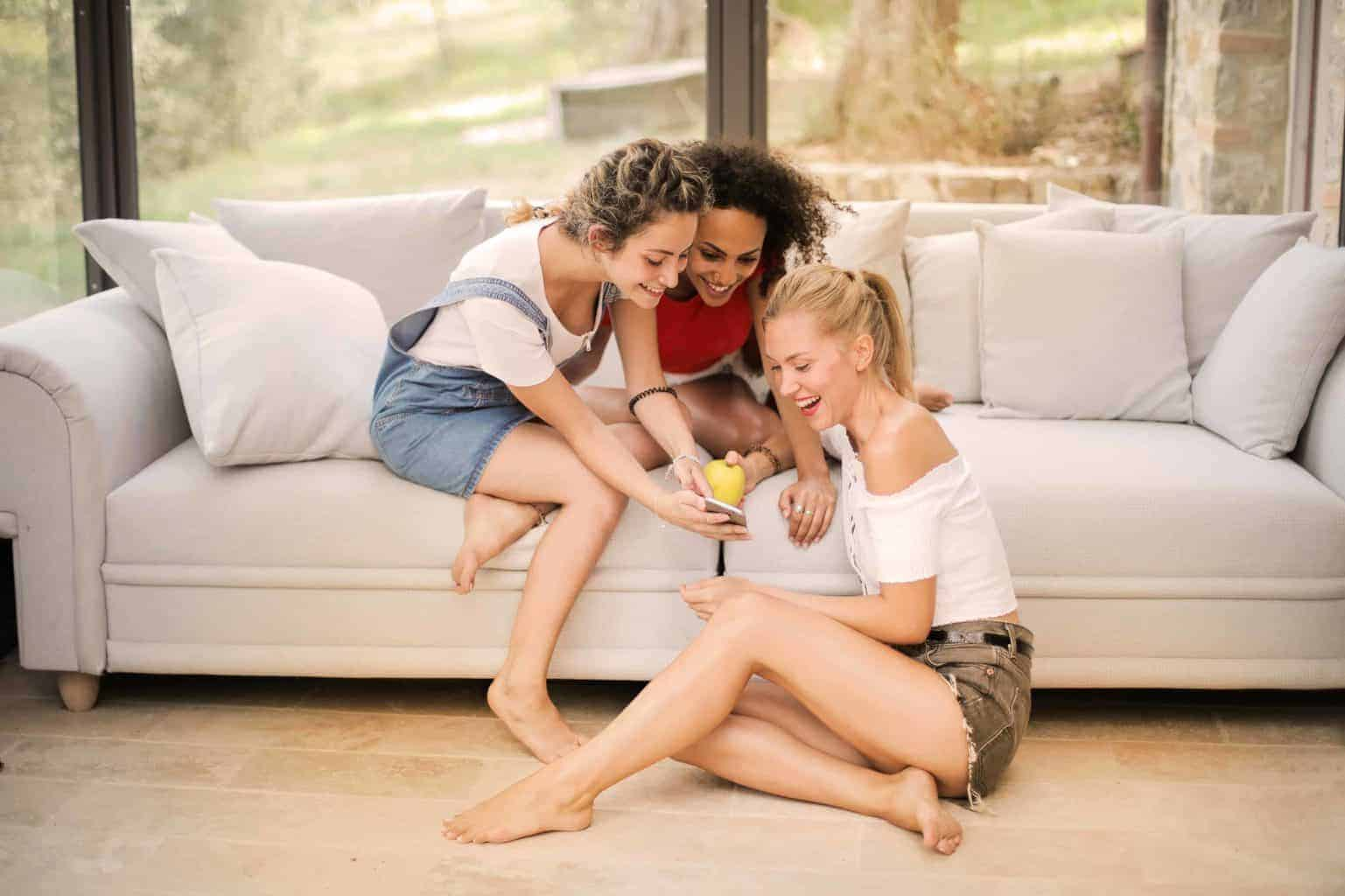 Three girls reading a text and smiling