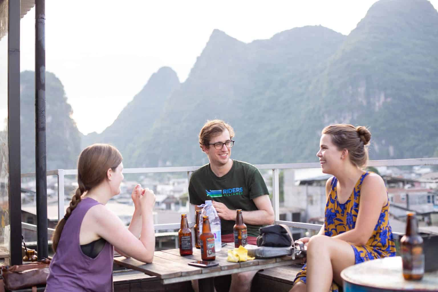 Three friends having a beer at a rooftop.