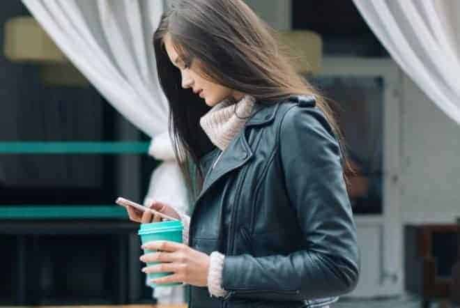 Girl carrying coffee looking down to text - Questions To Ask A Girl Over Text