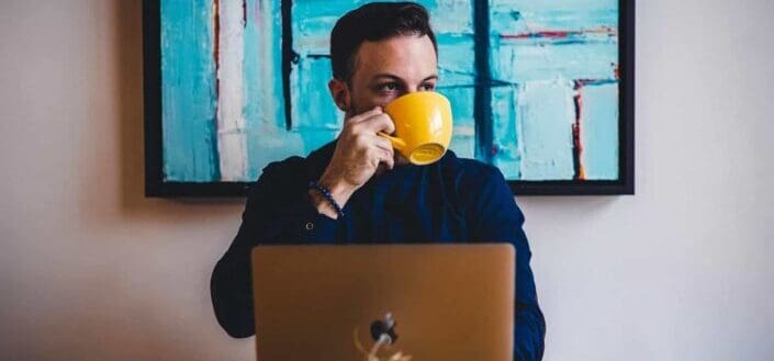 Guy drinking coffee from a yellow mug with his laptop in front