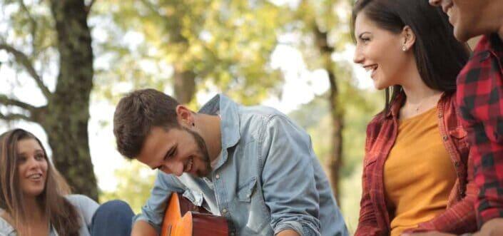 Friends having fun with man playing guitar