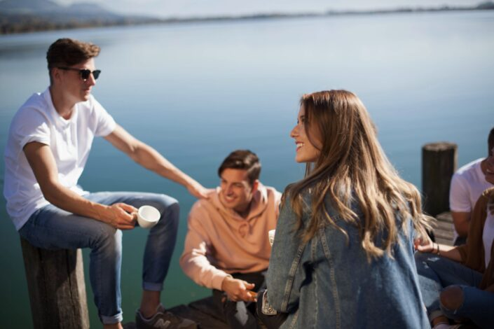 Friends sitting on a platform beneath a lake.