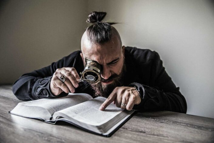 Man reading the bible using a magnifying glass.