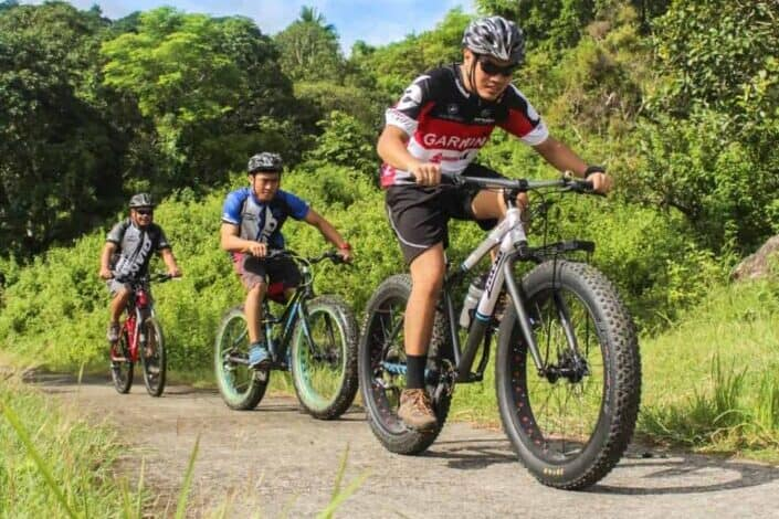 three men riding on bicycles