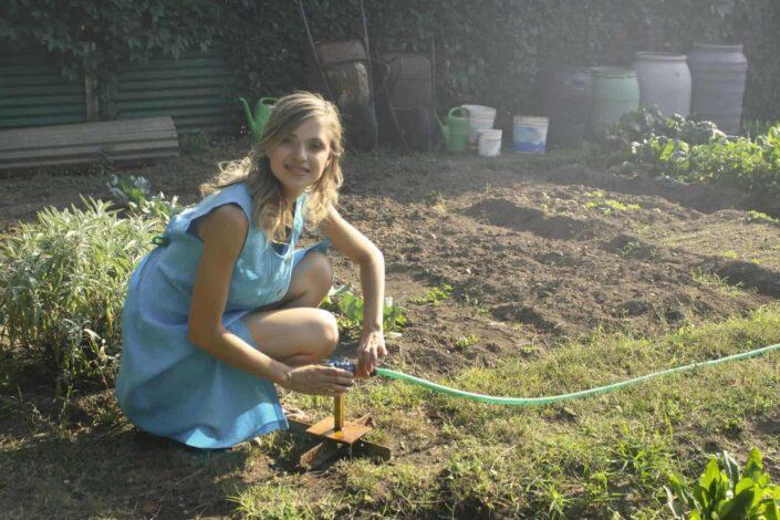 woman holding green garden hose