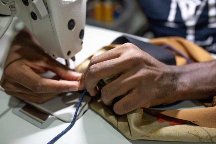 person sewing using machine