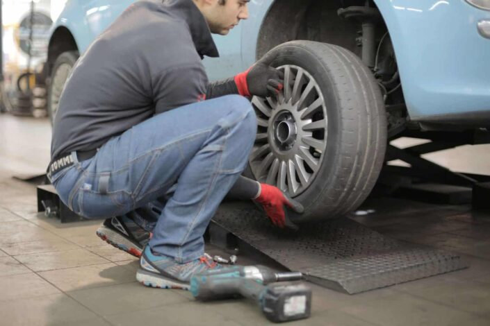 Man fixing the tire of the car