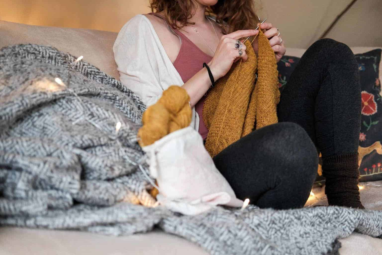 Woman sitting on couch crocheting