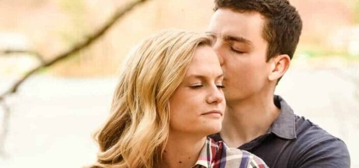 Man kissing side of his girl's head