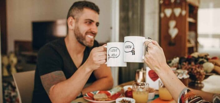 Man and cropped woman clinking mugs