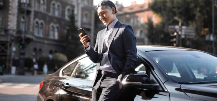 Successful businessman leaning against his car and looking at phone