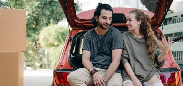 Couple talking at the back of car