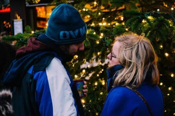couple looking face to face near christmas tree