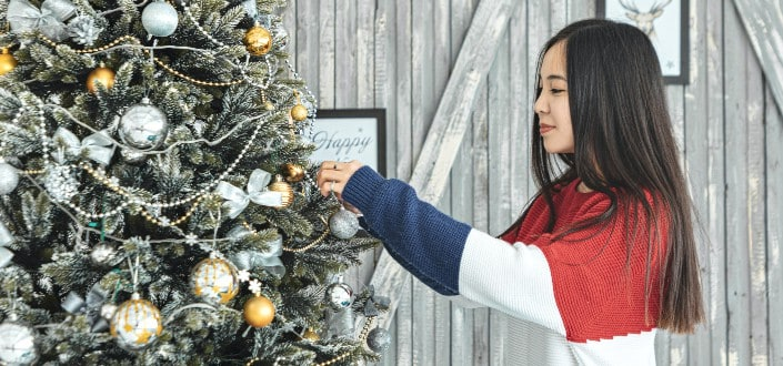 Young woman decorating her christmas tree