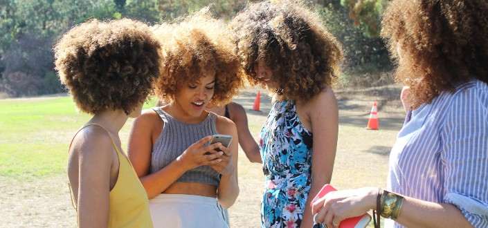 Young ladies looking at their friend's phone