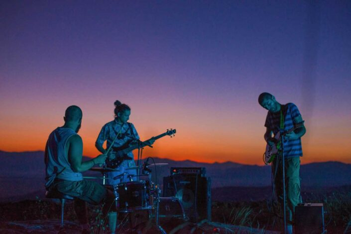 Boy band playing on hilly cliff at dusk