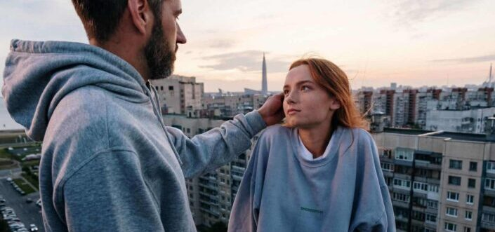 Man fixing his girl's hair at the rooftop