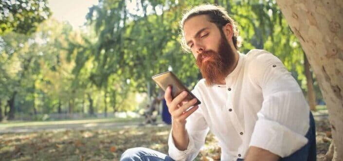 Bearded man checking his phone outdoors