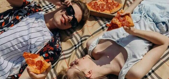 Couple lying on a blanket on sand eating pizza
