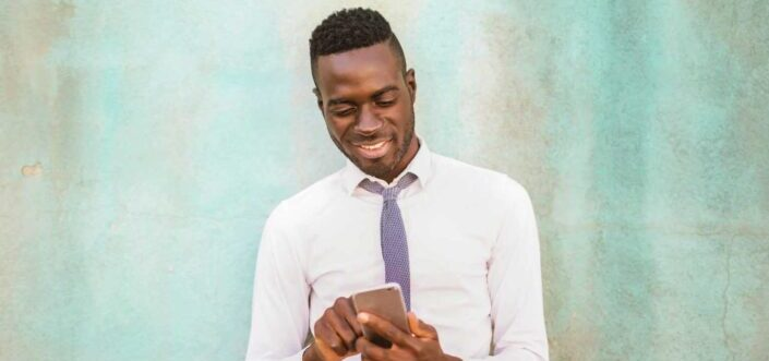 Man in formal attire surfing at his phone